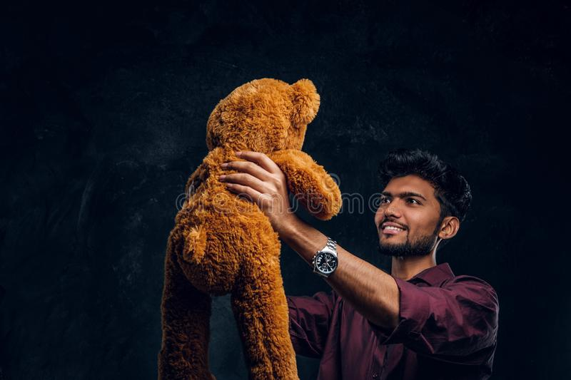 Indian guy in stylish shirt looks at his lovely teddy bear while holding it in hands. Studio photo against a dark. Young Indian guy in stylish shirt looks at his stock photo