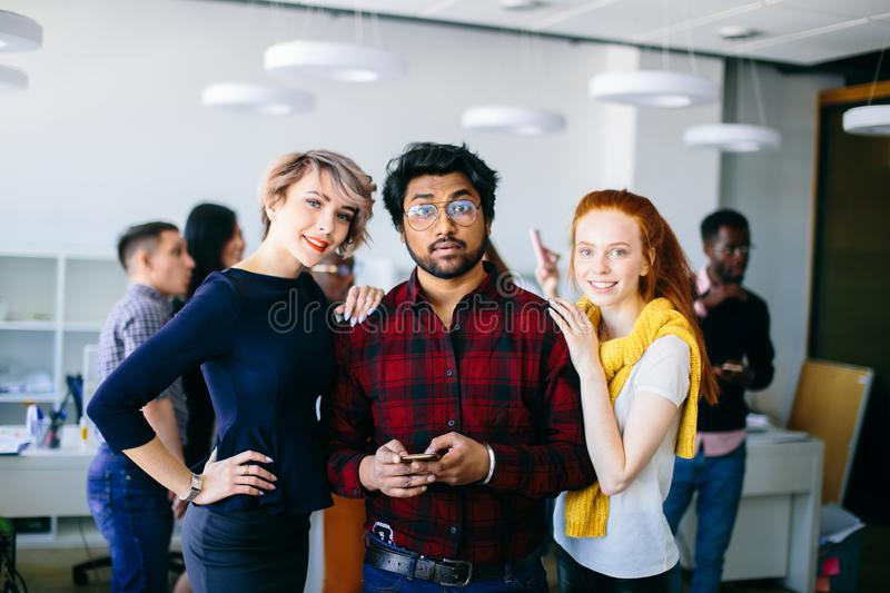 Indian handsome man using his smartphone. Indian handsome men with smartphone and attractive two women are looking at the camera. women holding hands on their stock photo