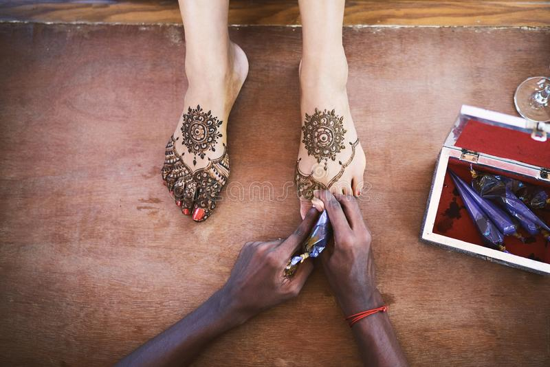 Henna artist Mehndi painting the foot of women on the indian wedding day royalty free stock image