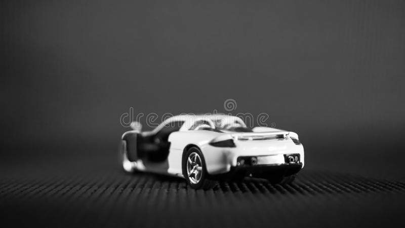 Rear view of a white toy Porsche, shown in dark black bacrkgoud. Indian high class is moving on for top end luxury cum sports car for their garages.  This one is royalty free stock image