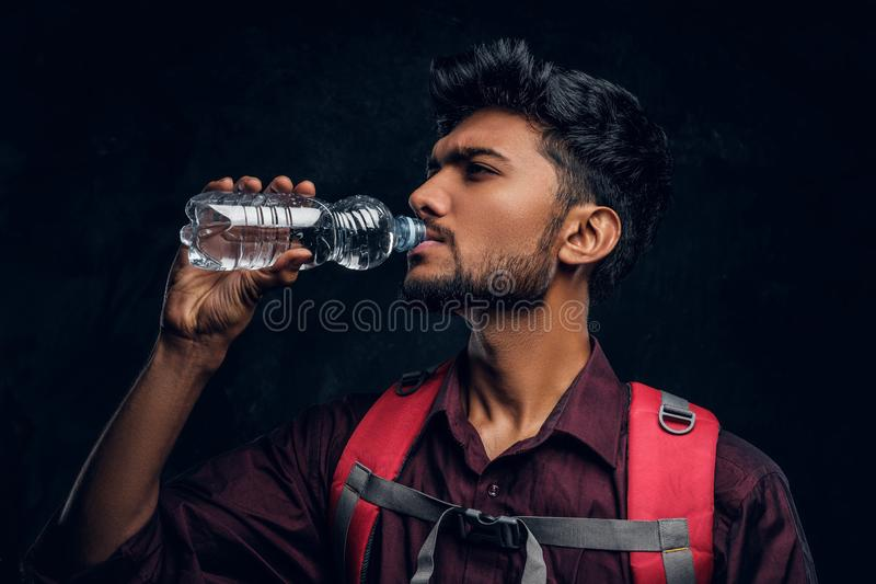 Indian hiker with backpack exhausted with thirst drinking water. Studio photo against a dark textured wall. Handsome Indian hiker with backpack exhausted with stock photo