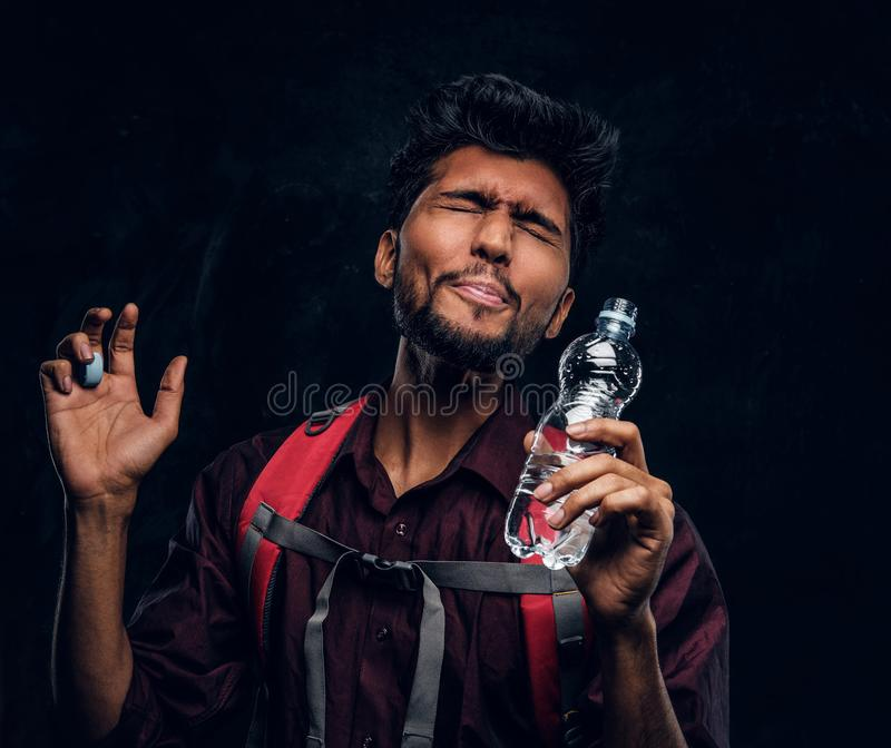 Indian hiker with backpack got a stirring sensation drank a sip of fresh water. Studio photo against a dark textured. Handsome Indian hiker with backpack got a royalty free stock photography