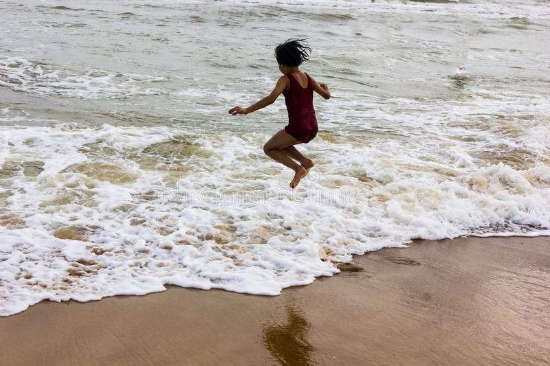 Indian kid girl jumping against approaching wave on puri sandy beach in seashore expressing joy and excitement.  stock photography