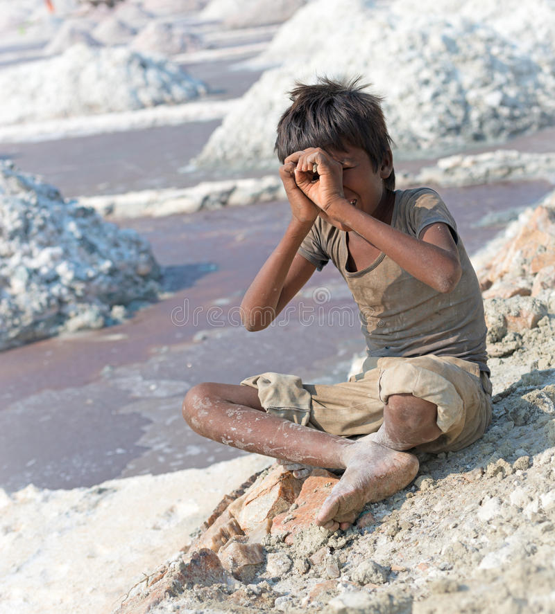 Indian kid on salt farm. Sambhar, India - Nov 19: Portrait of indian kid in salt farm on Nov 19, 2012 in Sambhar Salt Lake, India. It is India's largest saline royalty free stock image