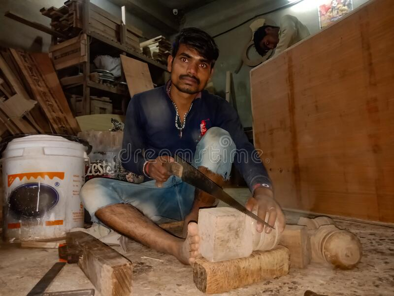 an indian labour chopping wood logs at art factory in India January 2020 royalty free stock photo