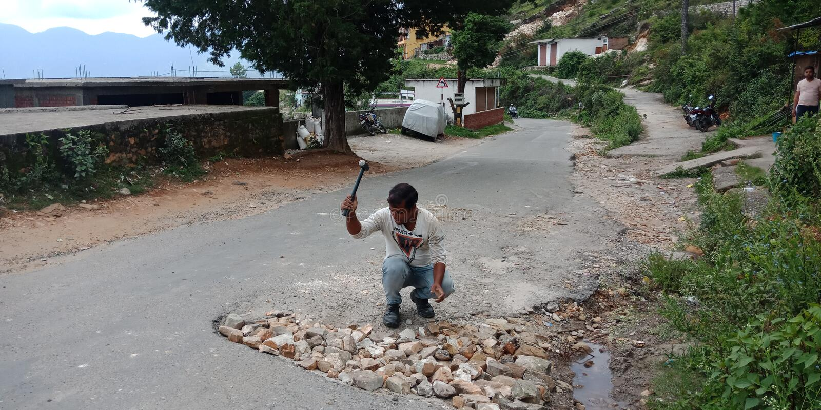 Indian labour filled the pothole royalty free stock photo