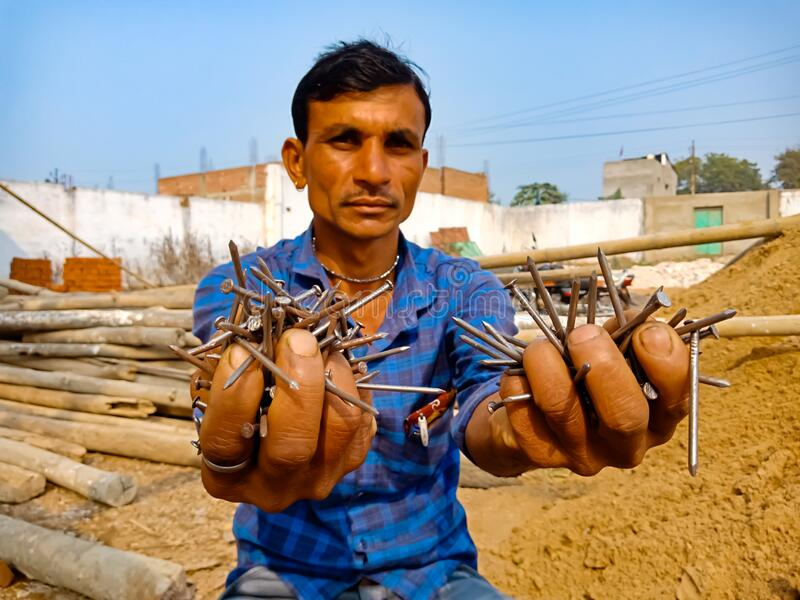 an indian labour presenting iron nails on hand at construction site in India January 2020 stock photos