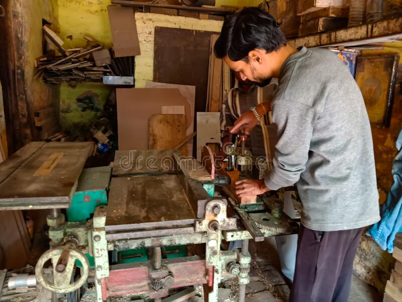 indian labour working at wooden cutting machine into the workshop in india January 2020 royalty free stock image