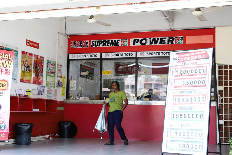 Indian Lady Walking Out From The Sports Toto Outlet. Ticket counters, signboard and posters at a Berjaya Sports Toto outlet in Malaysia stock images