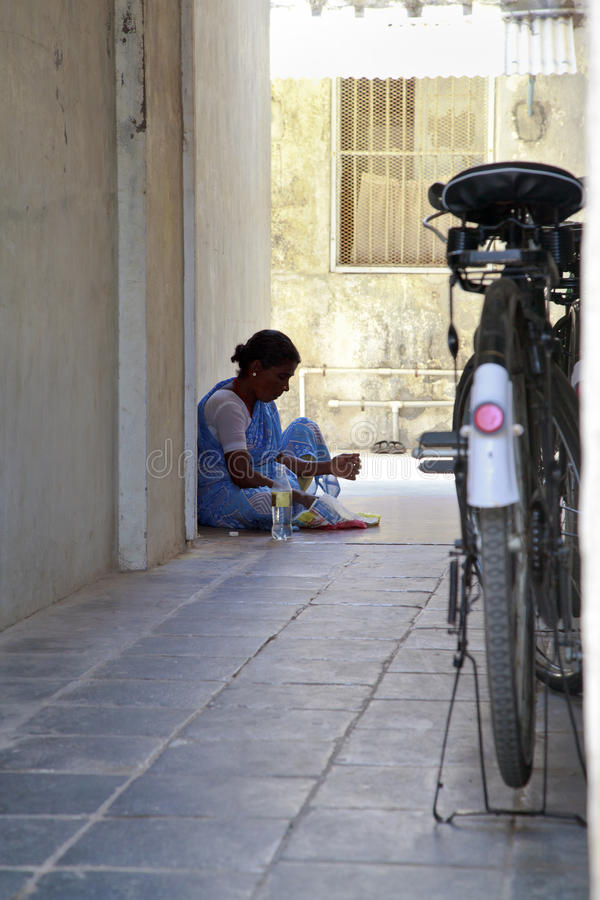 Indian maid having lunch from newsprint stock images