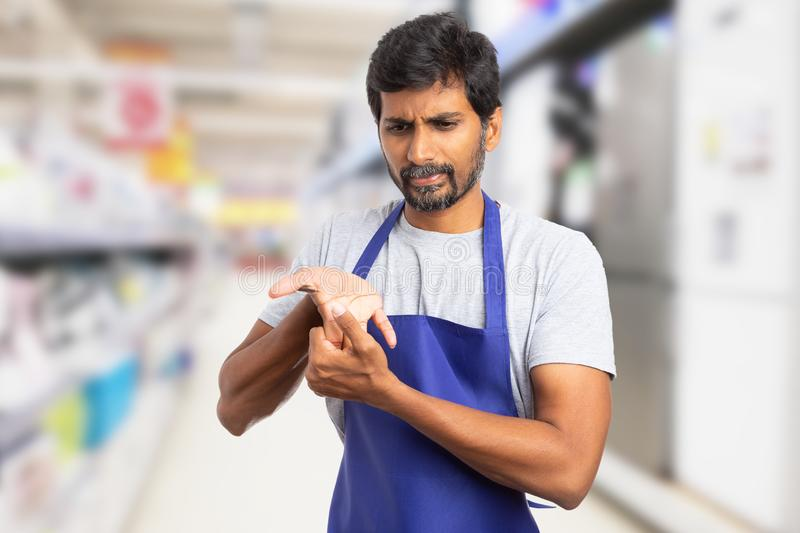 Hypermarket employee stretching fingers royalty free stock photography