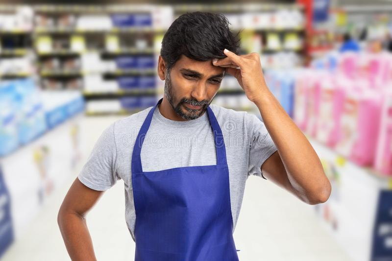 Hypermarket worker touching forehead as stress concept stock photography