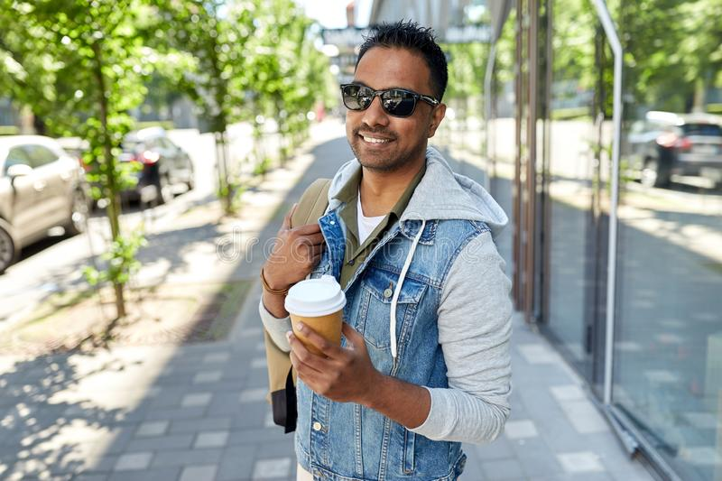Indian man with bag and takeaway coffee in city. Travel, tourism and lifestyle concept - smiling indian man with backpack and takeaway coffee on city street stock image