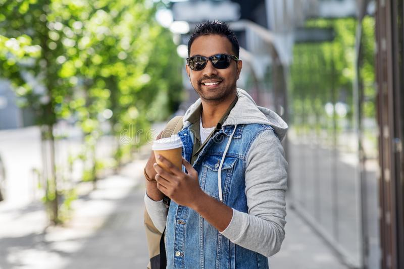 Indian man with bag and takeaway coffee in city. Travel, tourism and lifestyle concept - smiling indian man with backpack and takeaway coffee on city street royalty free stock photography