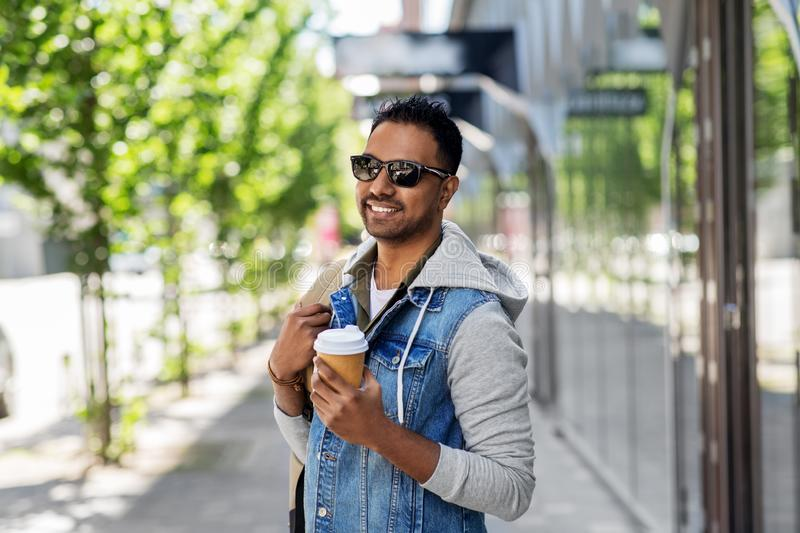 Indian man with bag and takeaway coffee in city. Travel, tourism and lifestyle concept - smiling indian man with backpack and takeaway coffee on city street stock photography