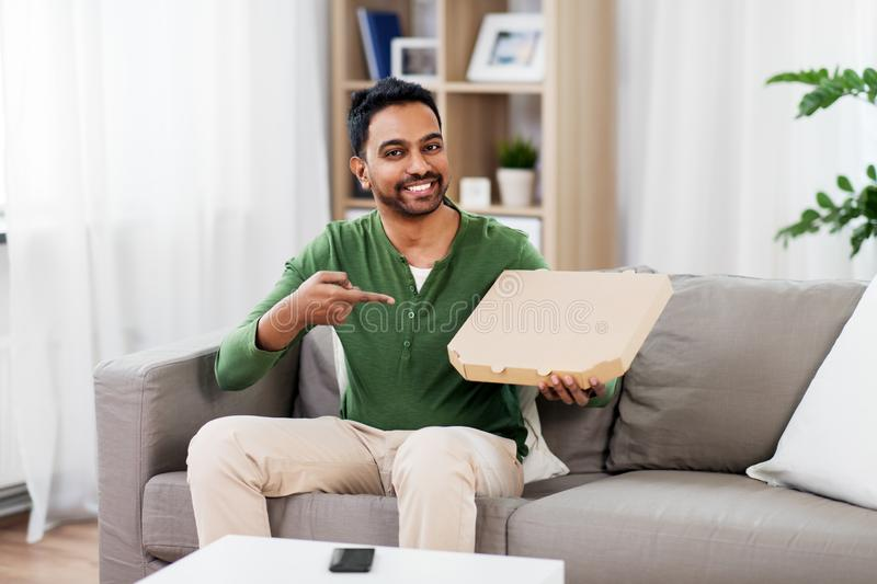 Indian man with box of takeaway pizza at home. Food delivery, consumption and people concept - smiling indian man with box of takeaway pizza at home stock images