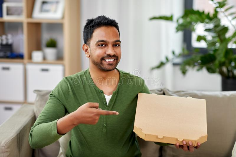 Indian man with box of takeaway pizza at home. Food delivery, consumption and people concept - smiling indian man with box of takeaway pizza at home stock photo
