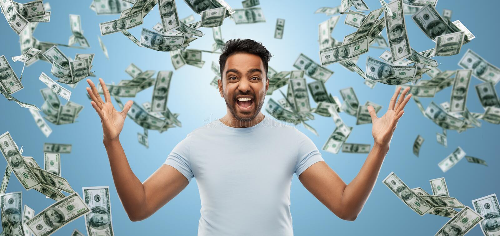 Indian man celebrating triumph over money falling. Success, wealth and finances concept - happy young indian man celebrating triumph over blue and cash money stock image