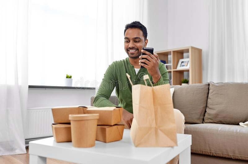 Indian man checking takeaway food order at home. Communication, leisure and people concept - indian man using smartphone for takeaway food order check up at home stock photography