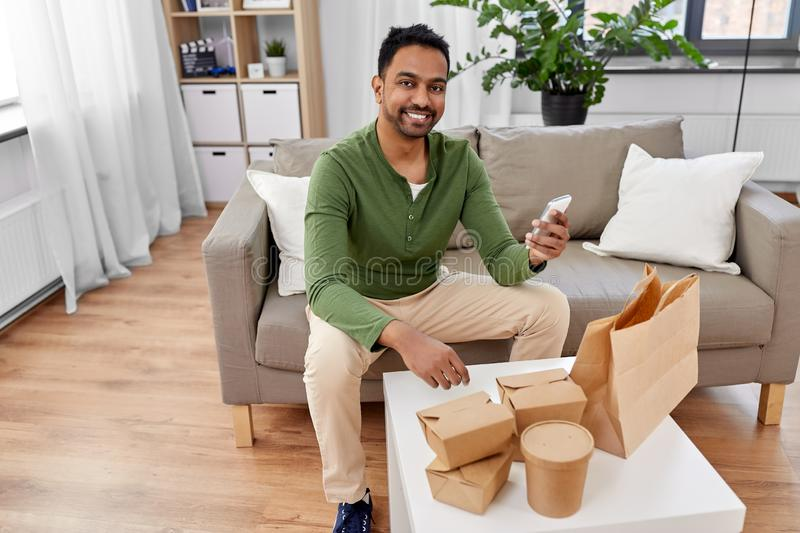 Indian man checking takeaway food order at home. Communication, leisure and people concept - indian man using smartphone for takeaway food order check up at home stock images