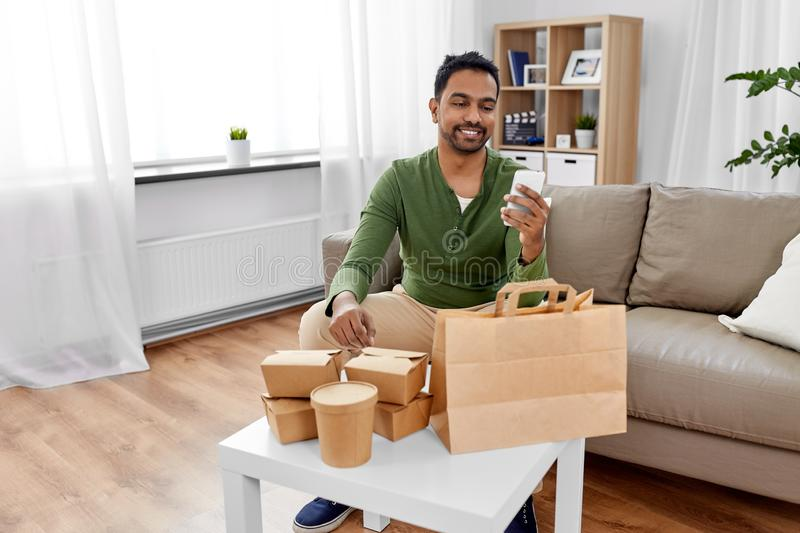 Indian man checking takeaway food order at home. Communication, leisure and people concept - indian man using smartphone for takeaway food order check up at home royalty free stock photos