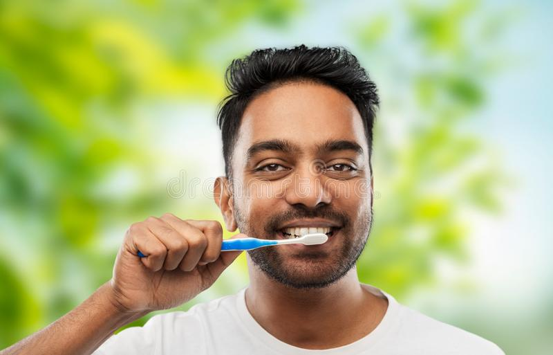 Indian man cleaning teeth over natural background. Oral care, dental hygiene and people concept - smiling young indian man with toothbrush cleaning teeth over royalty free stock images