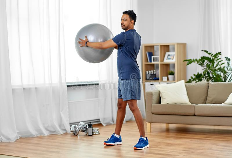 Indian man exercising with fitness ball at home stock image