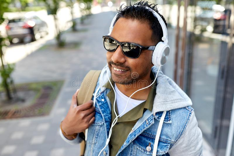 Indian man in headphones with backpack in city. Travel, tourism and lifestyle concept - smiling indian man in headphones with backpack listening to music on city royalty free stock photo