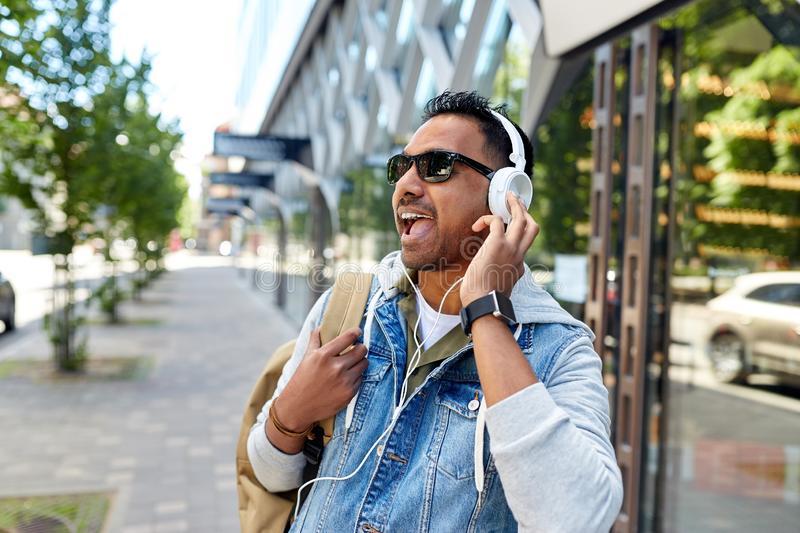Indian man in headphones with backpack in city. Travel, tourism and lifestyle concept - smiling indian man in headphones with backpack listening to music on city royalty free stock image