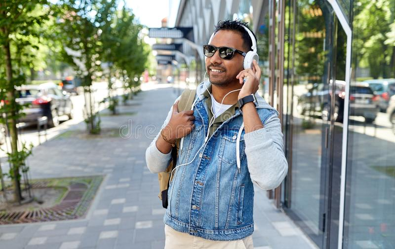 Indian man in headphones with backpack in city. Travel, tourism and lifestyle concept - smiling indian man in headphones with backpack listening to music on city royalty free stock photos