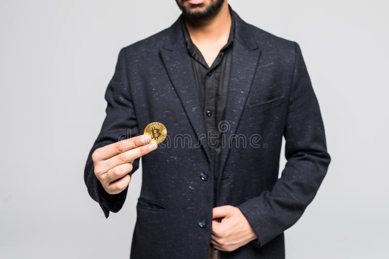 Indian business man holding golden bitcoin in hand isolated on a white background stock photos