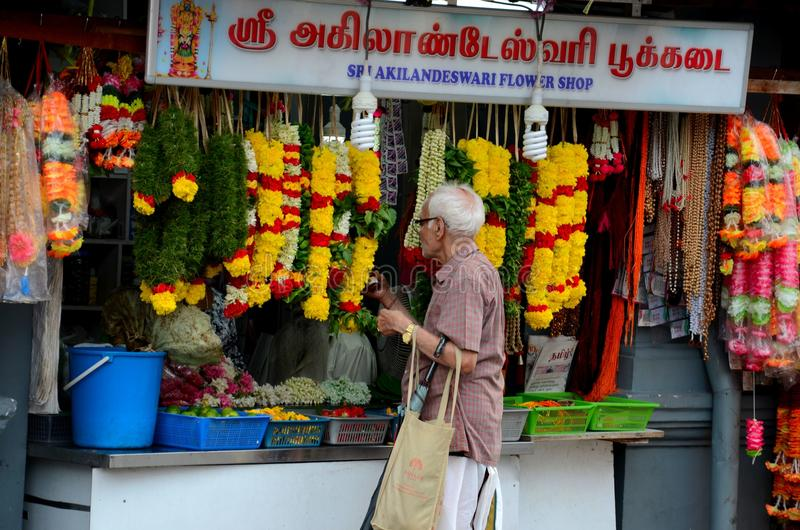 Indian man at Little India flower garland shop Singapore. Singapore - August 4, 2015: An elderly white haired Indian man in traditional dhoti and shirt carrying stock images