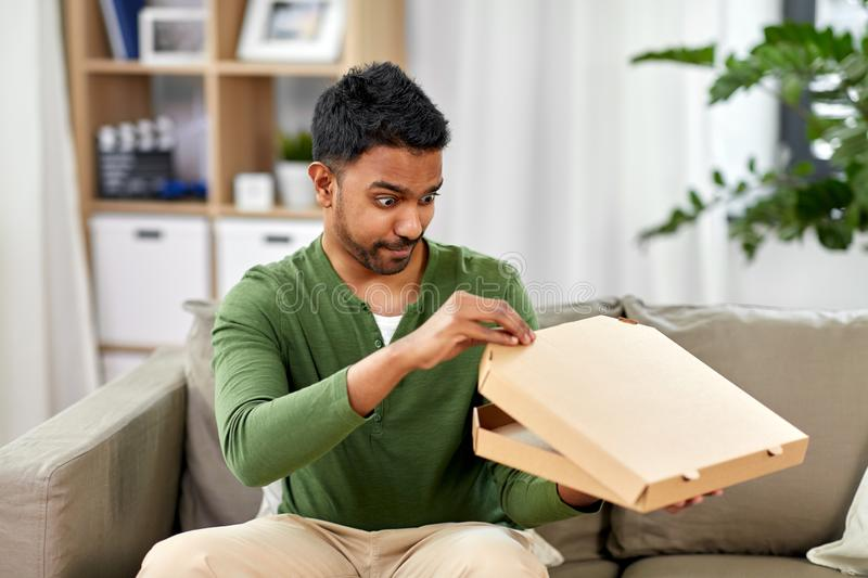 Indian man looking inside of takeaway pizza box. Food delivery, consumption and people concept - excited indian man looking inside of takeaway pizza box at home stock photo