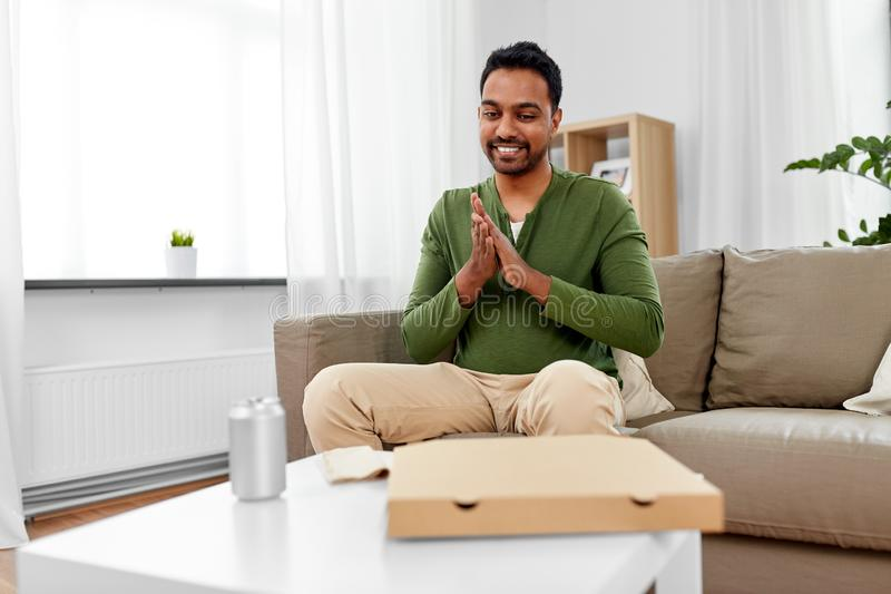 Indian man looking inside of takeaway pizza box. Food delivery, consumption and people concept - excited indian man looking inside of takeaway pizza box at home stock images