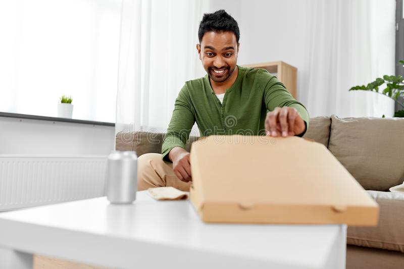 Indian man looking inside of takeaway pizza box. Food delivery, consumption and people concept - excited indian man looking inside of takeaway pizza box at home royalty free stock images