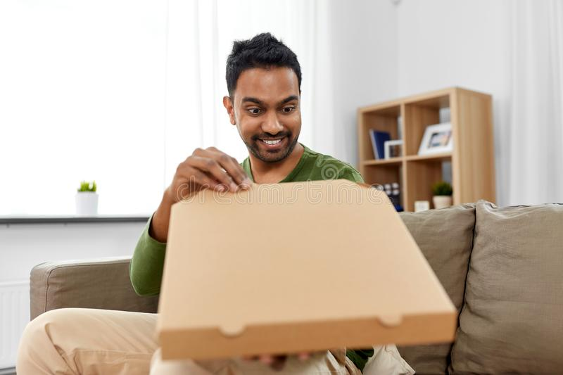 Indian man looking inside of takeaway pizza box. Food delivery, consumption and people concept - excited indian man looking inside of takeaway pizza box at home royalty free stock photos