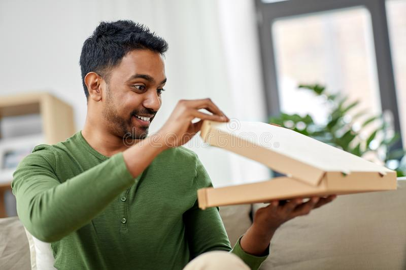 Indian man looking inside of takeaway pizza box. Food delivery, consumption and people concept - excited indian man looking inside of takeaway pizza box at home stock image
