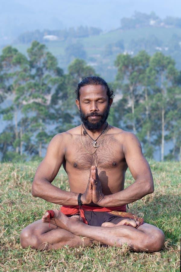 Indian man meditating in lotus yoga pose on green grass in Kerala, South India royalty free stock photos