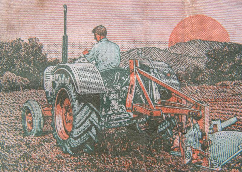 Indian Man Ploughing Field using tractor portrait. Green color Indian Man Ploughing Field using tractor and sun and mountains portrait on old 5 rupees India stock image