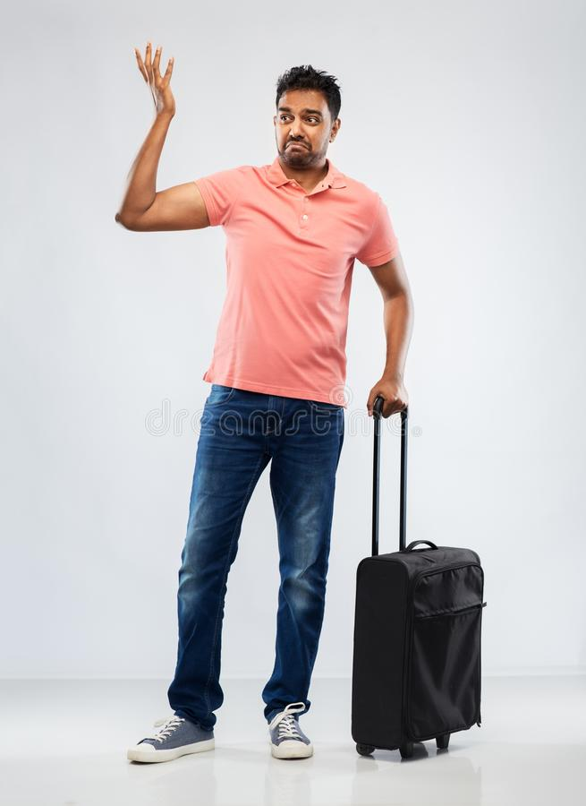 Indian man in polo shirt with travel bag shrugging. Family, tourism and vacation concept - puzzled indian man in polo shirt with travel bag shrugging over grey stock image