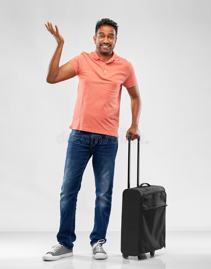 Indian man in polo shirt with travel bag shrugging. Family, tourism and vacation concept - puzzled indian man in polo shirt with travel bag shrugging over grey royalty free stock images