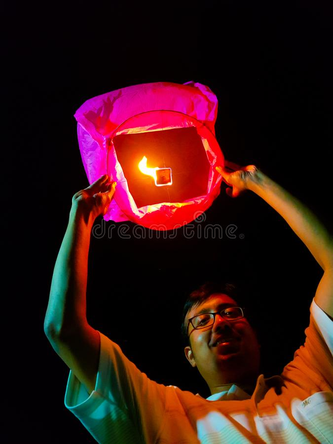 An indian man releasing a lighted paper hot air balloon in sky lantern festival.  royalty free stock image
