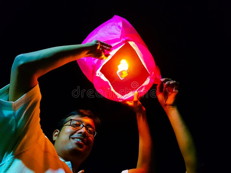 An indian man releasing a lighted paper hot air balloon in sky lantern festival.  royalty free stock photo