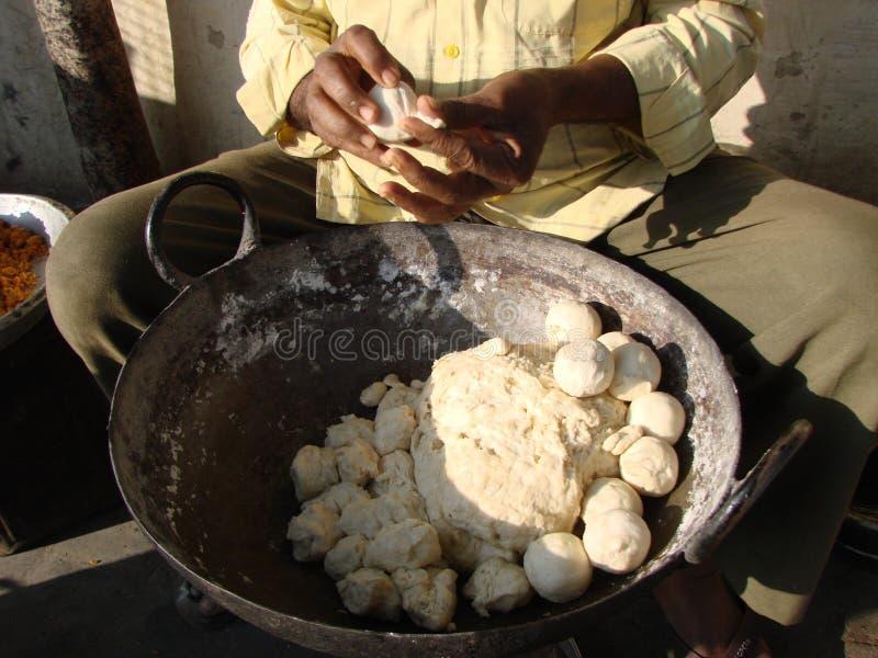 Indian man rolls dough balls samosa for breakfast stock photo
