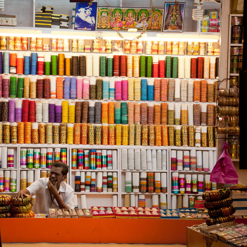 Indian man selling souvenirs and colorful bangles at market place stock image