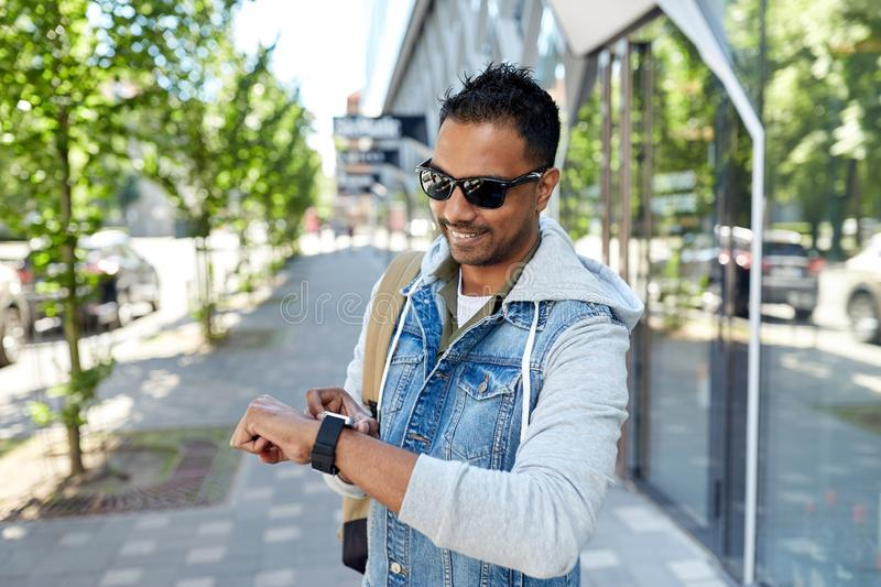 Indian man with smart watch and backpack in city. Travel, tourism and lifestyle concept - smiling indian man with smart watch and backpack walking along city royalty free stock image