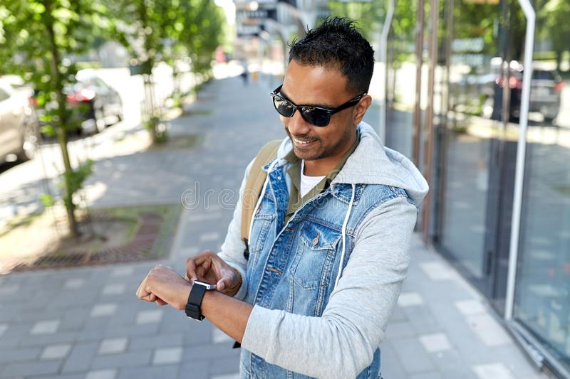 Indian man with smart watch and backpack in city. Travel, tourism and lifestyle concept - smiling indian man with smart watch and backpack walking along city stock photos