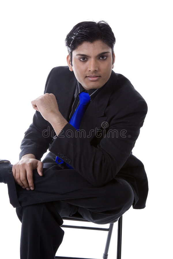 Indian man in a suit. Young male Indian model sitting in a chair, wearing a black business suit with a blue tie stock photos