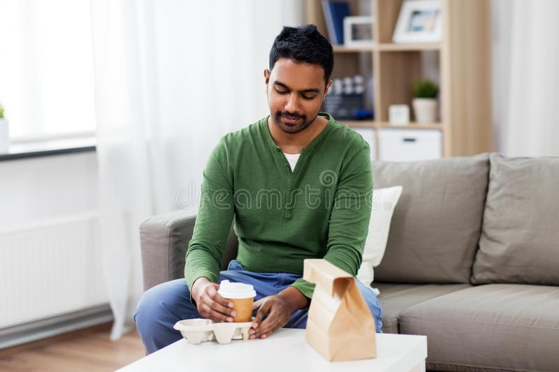 Indian man with takeaway coffee and food at home. Consumption and people concept - smiling indian man with takeaway coffee and food at home stock photos