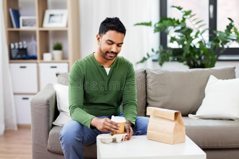 Indian man with takeaway coffee and food at home. Consumption and people concept - smiling indian man with takeaway coffee and food at home royalty free stock photography